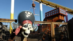 Stock Video Footage of Swinging Pirate boat ride, with comical skull of pirate, seen at the amusemen