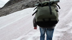 Steep slippery snow-covered mountain slope with climber Stock Footage