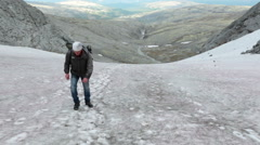 Mountaineer walking on snow field at steep mountain slope Stock Footage