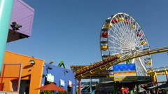 Wide shot of Amusement park with large Ferris wheel with roller coaster visible Stock Footage
