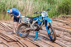 Man washing a race bike after the competition in motocross Stock Photos