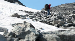 Steep slope of mountain with sharp stones and snowy location, hiker climbing up Stock Footage