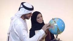 Emirati couple looking at globe. Stock Footage