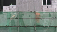 Construction workers on scaffolding, China - stock footage
