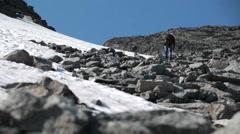 Man a hiker climbing to snow covered mountain. Khibiny massife, Kola peninsula Stock Footage