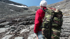 Mountaineer looking at the range top and continues climbing through the stones Stock Footage