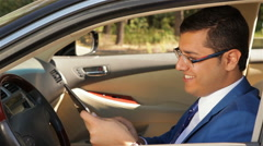 Businessman sitting in the car reading tablet Arkistovideo