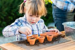 Girl planting flower seeds into pots with her mother Stock Photos
