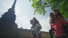 4k Happy energetic group of friends in London, playing piggyback races Stock Footage
