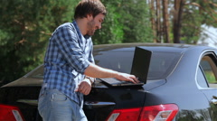 Stock Video Footage of man working on the computer in the trunk of car
