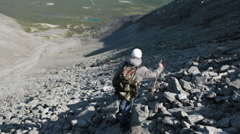 Rocky downhills. Hiker with stick stepping carefully on steep descent. Khibiny Stock Footage