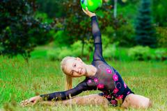 outdoor portrait of young cute little girl gymnast training with ball in park - stock photo
