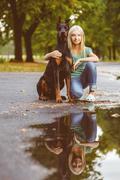 blonde girl hugs her beloved dog or doberman in summer park. Warm toned image - stock photo
