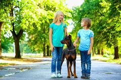 Blonde girl and boy posing with beloved dog or doberman in summer park Stock Photos