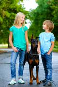 blonde girl and boy posing with beloved dog or doberman in summer park - stock photo