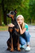 blonde girl hugs her beloved dog or doberman in summer park - stock photo
