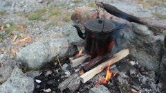 Loop view at the smoke-black kettle hanging wooden stick over bonfire - stock footage