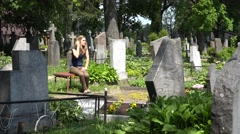 Young girl visit fellow lover man grave in cemetery. 4K - stock footage