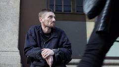 Disable homeless waiting for charity on the sidewalk Stock Footage