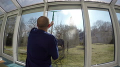 Man spray cleaner and wipe window with squeegee tool. 4K Stock Footage