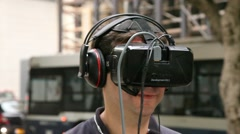 Stock Video Footage of A man watches in the street a demonstration of virtual reality movie