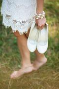 barefoot young girl wearing white beautiful dress holding shoes in hands - stock photo