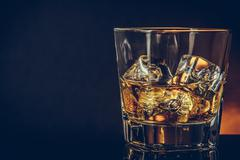 Glass of whiskey on black background with reflection, warm atmosphere Stock Photos