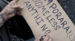 Close-up homeless man writing sign temporarily homeless anything helps 4K Stock Footage