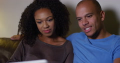 An affectionate young couple browsing on their laptop at home. Shot on RED Epic. Stock Footage