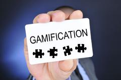 Young man in suit shows a signboard with the word gamification Stock Photos