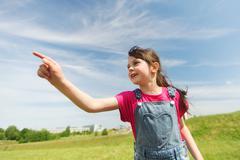happy little girl pointing finger on summer field - stock photo