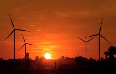 Eco power in wind turbine farm with sunset Stock Photos
