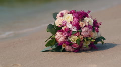 Bridal bouquet lying on the sand Stock Footage