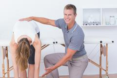 Happy doctor stretching a woman back Stock Photos