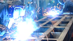 Sparks fly as a Welder welds metal in an industrial factory - stock footage