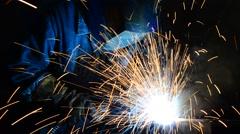 Welder welding metal structures in industrial fabrication factory Stock Footage