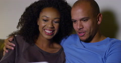 An attractive African American couple watching a movie on a digital tablet. Stock Footage