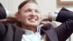 Stock Video Footage of Pleased businessman relaxing in a chair