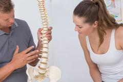 Stock Photo of Doctor showing anatomical spine to his patient