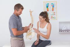 Doctor showing anatomical spine to his patient - stock photo