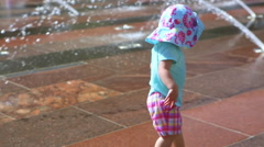 Cute toddler girl playing with small fountains in splash park. Stock Footage
