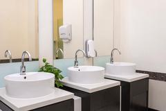 white basins in bathroom interior with granitic tiles - stock photo