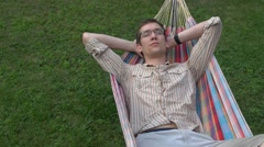 Hammock. man sleeping wakes up and stretches. copy space left. isolated view Stock Footage