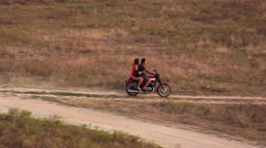 Happy man and woman traveling on an old red bike to the river Stock Footage