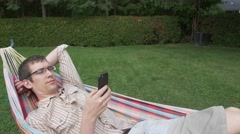 Young man plays on smart phone phone in hammock Stock Footage