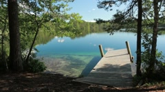 Shore of clear-watered lake Valkiajärvi with a wooden dock Stock Footage