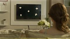 Rear view of young woman watches TV in the room. With tracking marks - stock footage