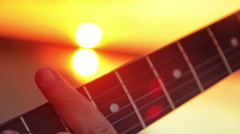 Man close-up electric guitar playing rock at sunset and lake in the summer Stock Footage