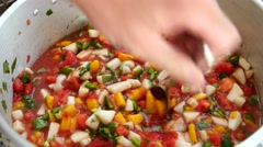 Man stirs colorful peach salsa in kitchen Stock Footage