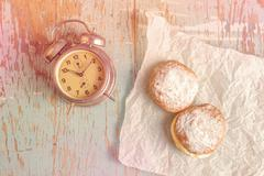 Sweet sugary donuts and vintage clock on rustic table Stock Photos